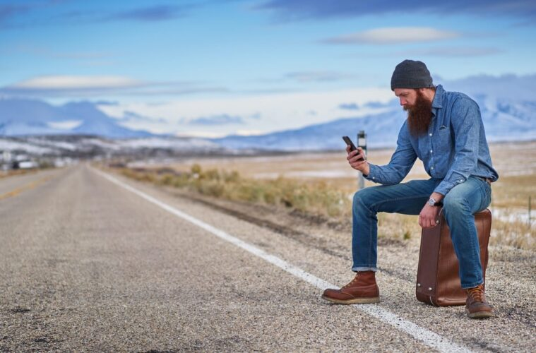 Traveller with smartphone using apps