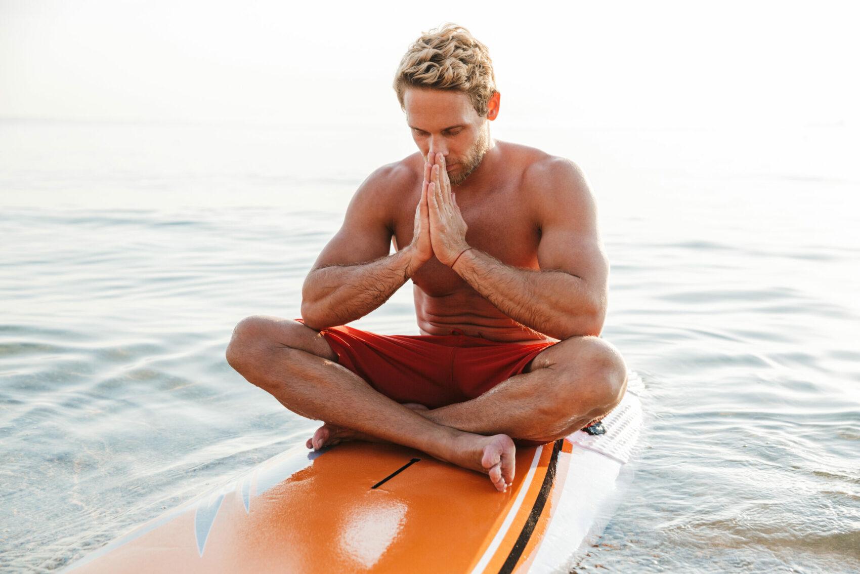 Man meditating on surf board