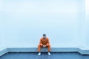 Prisoner sitting on bench in prison room