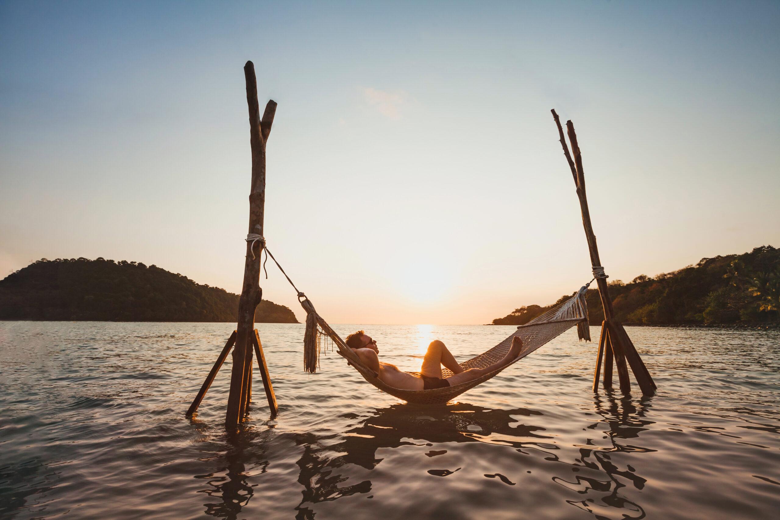 Man in hammock over sea