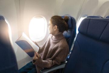 Woman reading magazine on plane