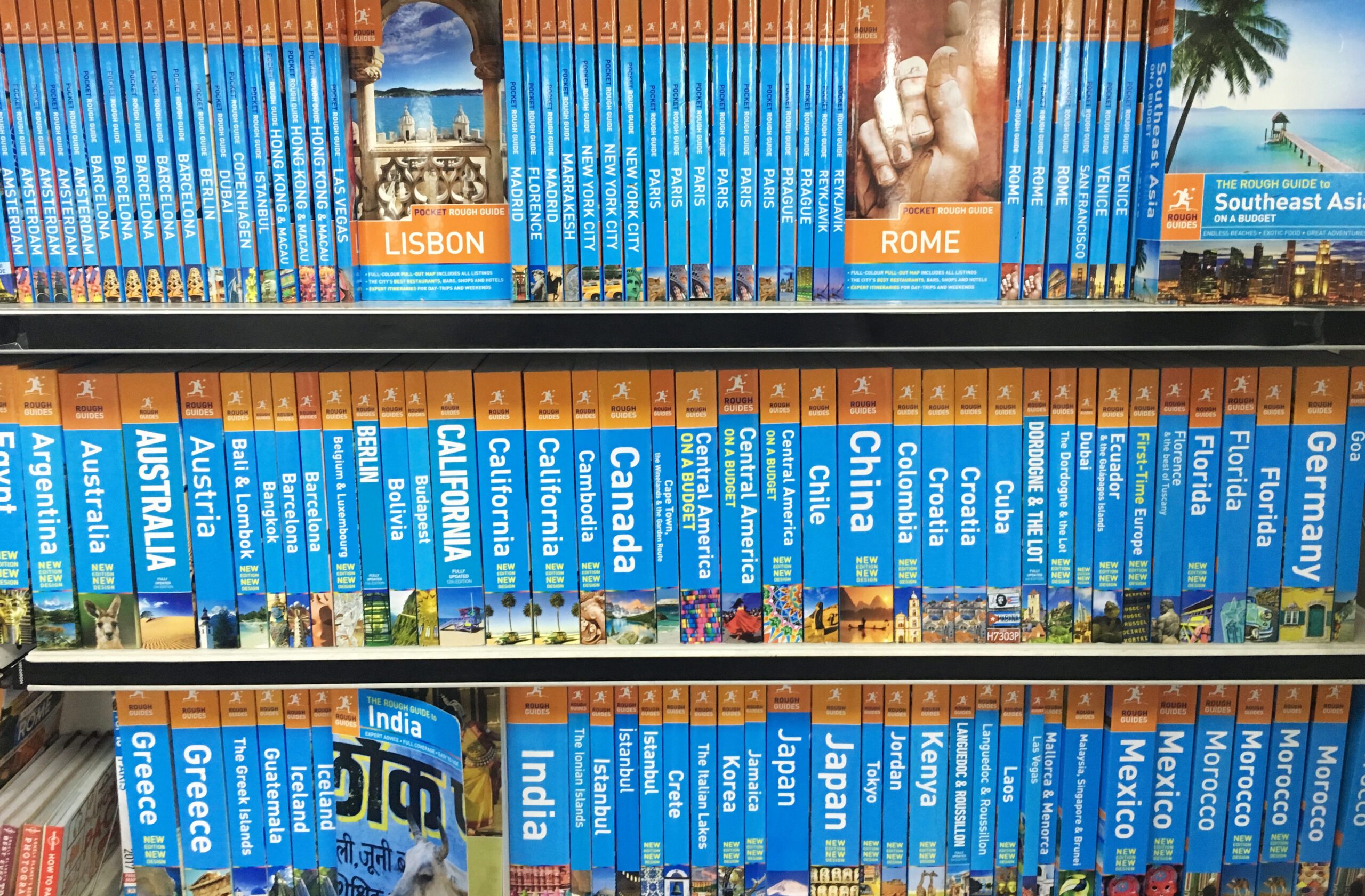 Rough Guide travel books on various countries stacked on a shelf