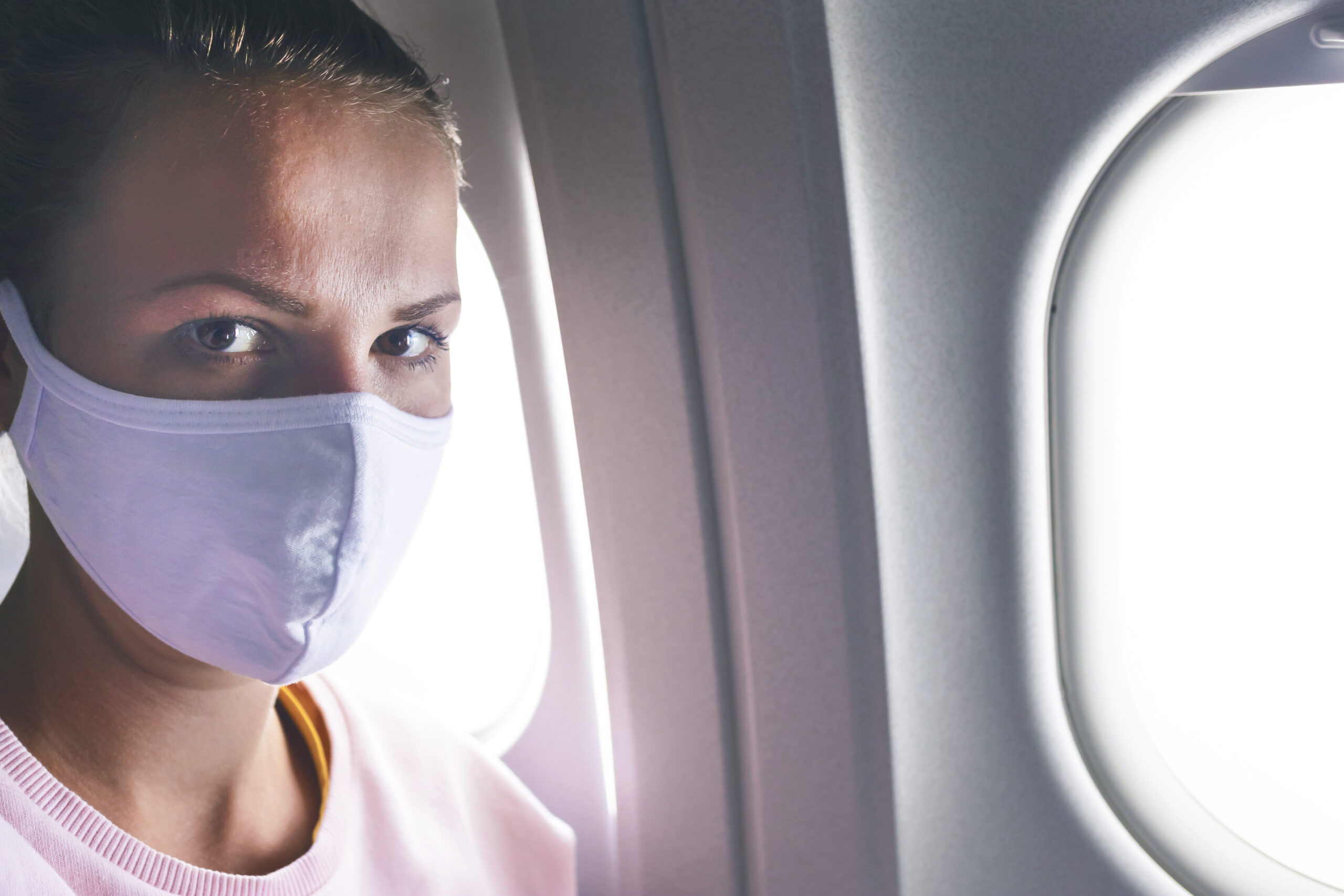 Woman in face mask on plane