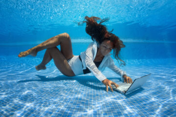 Woman underwater with laptop
