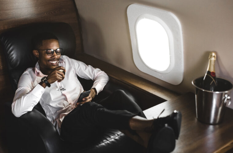 Black man on private jet drinking champagne
