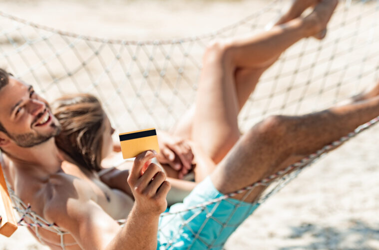 Young couple in hammock holding credit card