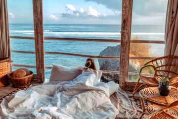 Woman enjoying morning vacations on tropical beach bungalow looking ocean view Relaxing holiday at Uluwatu Bali ,Indonesia