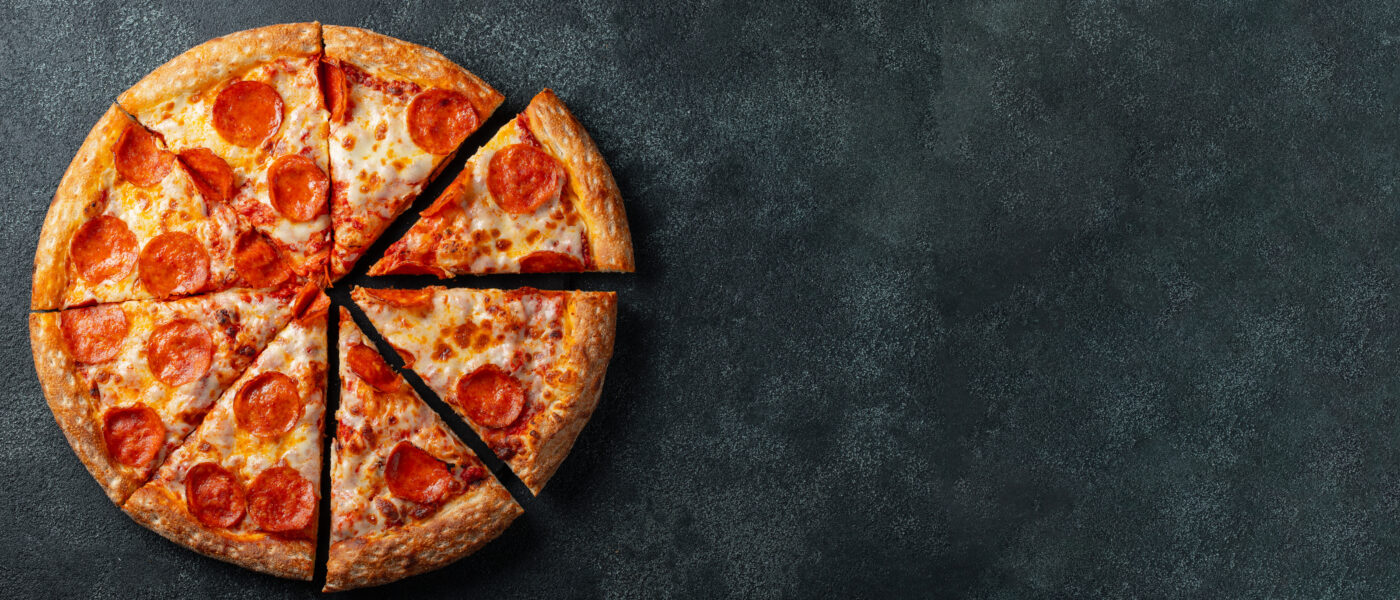 Tasty pepperoni pizza and cooking ingredients tomatoes basil on black concrete background. Top view of hot pepperoni pizza. With copy space for text. Flat lay. Banner.