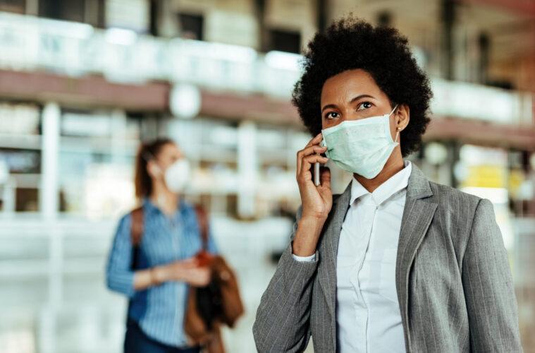 Passenger talking on smart phone while wearing face mask at the airport during virus epidemic.