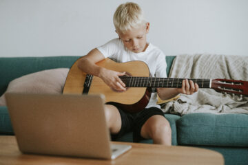 Boy learning to play guitar through a video call