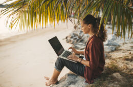 Woman sitting with laptop on the summer beach at sunset