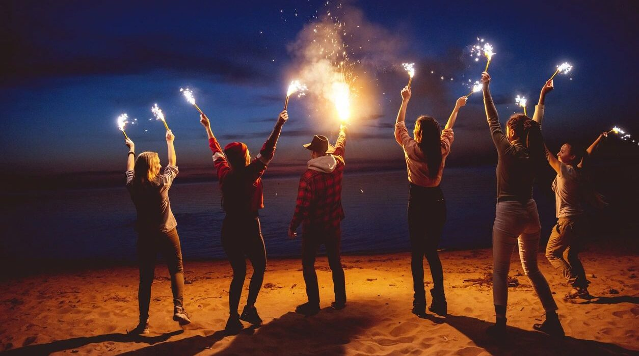Friends on beach with flares