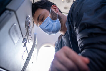 Man in mask on plane